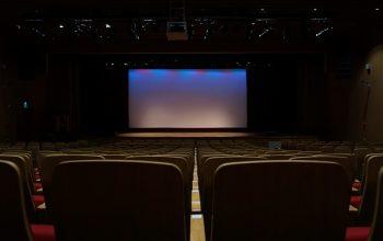 sala de cine con ascensor de videobeam en techo e iluminación de escena.