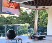 Balcon con elementos de gimnasio y con televisor soportado en techo